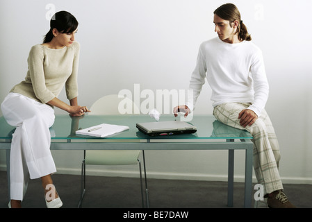 Colleagues flicking paper ball back and forth across table - Stock Photo