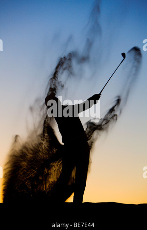 Silhouette of a golfer late in the day - Stock Photo