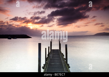 Looking out along the jetty walkway in Rhos on sea harbour at sunrise. - Stock Photo