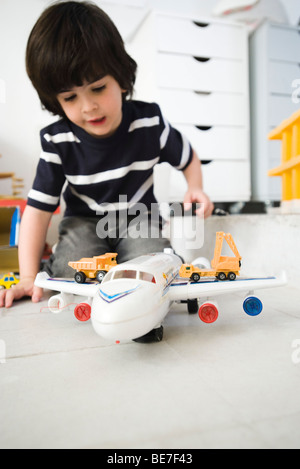 Little boy playing with toy airplane and toy trucks - Stock Photo