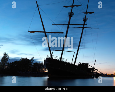 Grounded tall ship silhouette against twilight sky - Stock Photo
