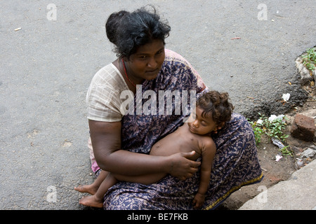 Woman with baby begging in the street in Pondicherry India - Stock Photo
