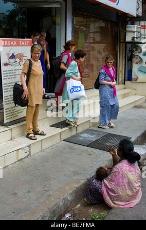 Beggar and western tourists in Pondicherry India - Stock Photo