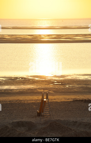 A childrens' slide on a beach on the island of Langeoog in the North Sea at sunset - Stock Photo