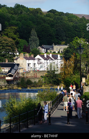 People walking on a Sunday afternoon along the Riverside park on the banks of the River Dee in Llangollen town, - Stock Photo
