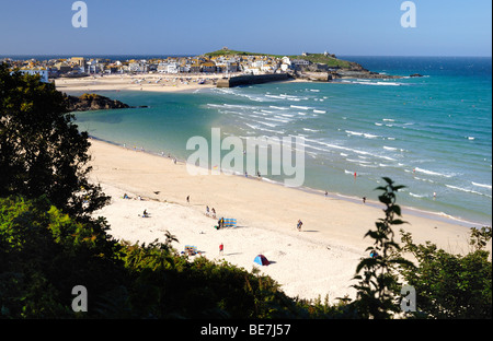 Tourists on a sandy beach with St Ives in the background - Stock Photo