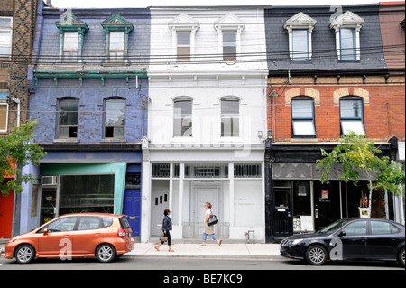 Pedestrians walking by storefront residential buildings along the stylish West Queen West district of downtown Toronto, - Stock Photo