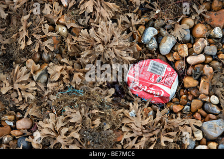 A discarded Coke can on a seaweed and pebble covered beach - Stock Photo