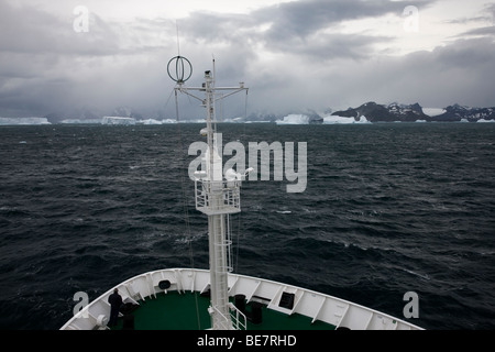 Antarctic cruise ship sails toward approaching storm and sea of big icebergs in iceberg alley near South Georgia - Stock Photo