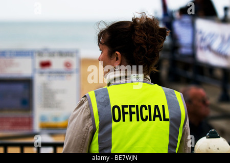 A woman wearing a hi-viz jacket with official written on the back. - Stock Photo