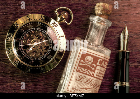 Pocket watch, fountain pen and a bottle of poison - Stock Photo