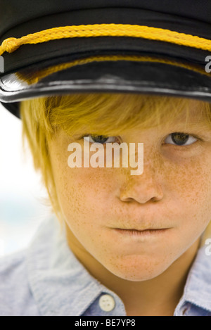 Boy wearing police officer's cap looking sternly at camera - Stock Photo