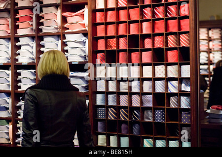 Woman in a mens clothes shop, looking at shirts and ties, Ingolstadt, Bavaria, Germany - Stock Photo
