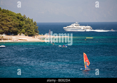 A ship and surfer off the beach at the Golden Horn, Bol, Brac Island, Dalmatia, Croatia, Europe - Stock Photo