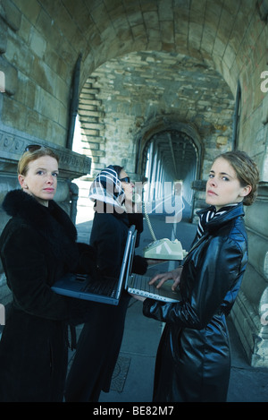 Three women standing in tunnel, two using laptop computers, one using landline phone - Stock Photo