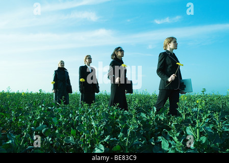 Four businesswoman in line walking through field, all carrying laptop computers and flowers - Stock Photo