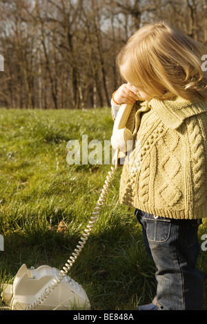 Little girl standing outdoors, using landline phone, side view - Stock Photo