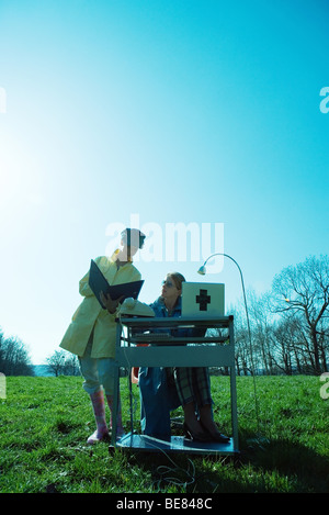 Outdoor office scene, office workers looking at folder together - Stock Photo