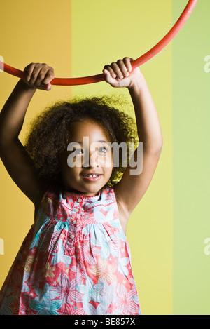 Little girl holding plastic hoop above her head - Stock Photo