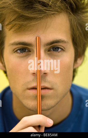 Young man holding pencil up to forehead - Stock Photo