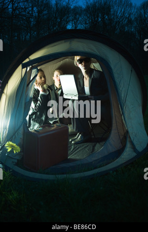 Female associates working in tent at night - Stock Photo
