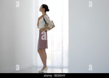 Woman standing beside window, looking up, side view - Stock Photo