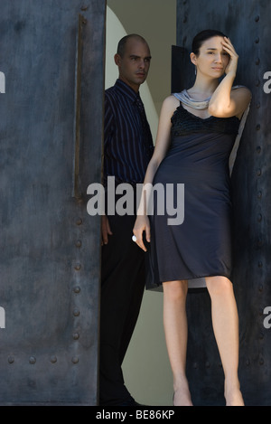 Woman standing in doorway, holding head, man frowning behind her - Stock Photo