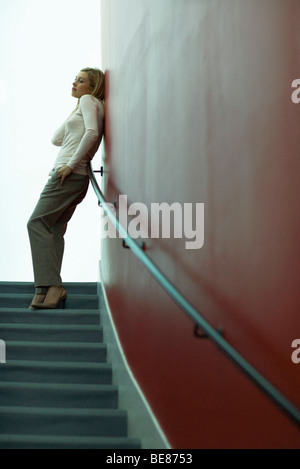 Woman standing at top of stairs, leaning against wall, looking away - Stock Photo