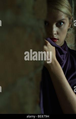 Woman hiding behind brick wall, staring at camera with wide eyes - Stock Photo