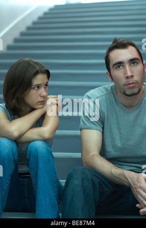 Young couple sitting side by side on stairs, man looking away, woman watching with concern - Stock Photo