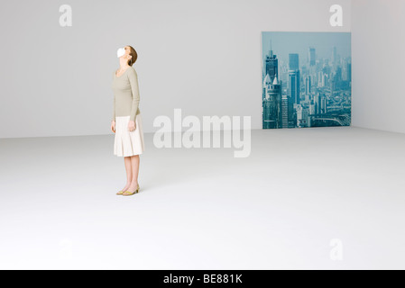 Woman wearing pollution mask looking up, cityscape in background - Stock Photo