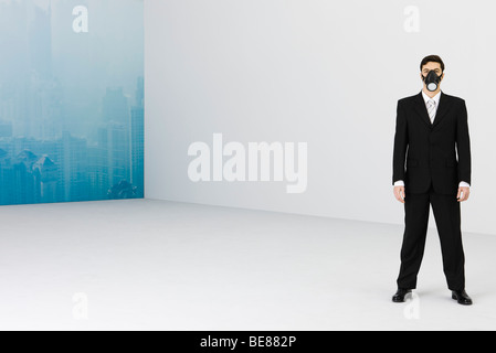 Businessman wearing gas mask, cityscape obscured by smog in background - Stock Photo