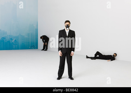 Businessmen wearing gas mask, cityscape obscured by smog in background - Stock Photo