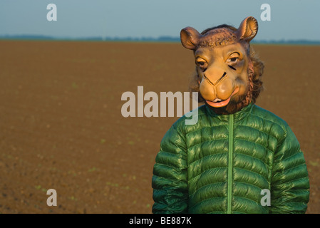 Person standing in field, wearing camel mask - Stock Photo