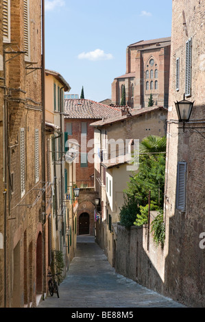 Narrow back street in the old town with the church of San Domenico behind, Siena, Tuscany, Italy - Stock Photo
