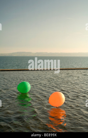 Two balloons floating on lake, breakwater in background - Stock Photo