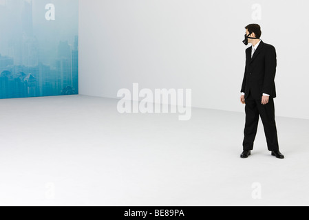 Businessman wearing gas mask, looking over shoulder at cityscape obscured by smog in background - Stock Photo