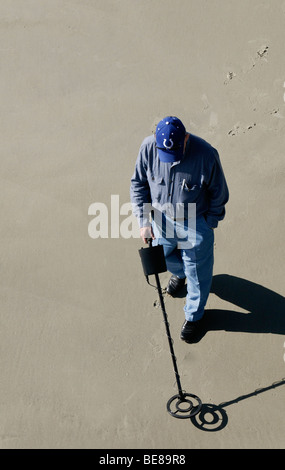 USA Georgia Tybee Island Man using metal detector on sandy beach - Stock Photo