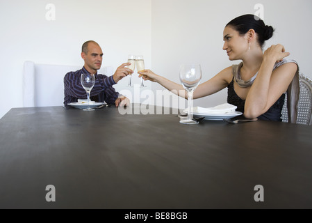 Couple sitting at table, clinking glasses of champagne - Stock Photo