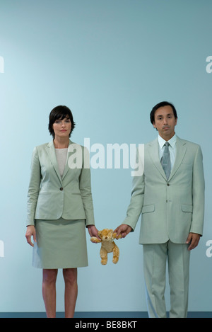 Professional couple standing together holding teddy bear between them - Stock Photo