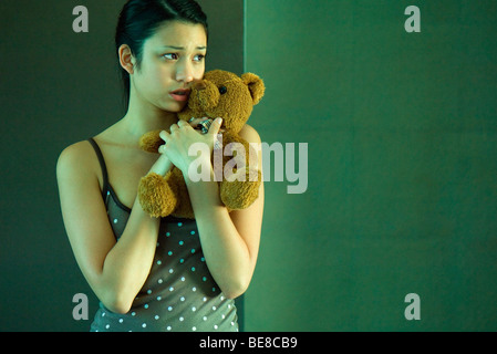 Young woman clutching teddy bear, anxiously looking away - Stock Photo