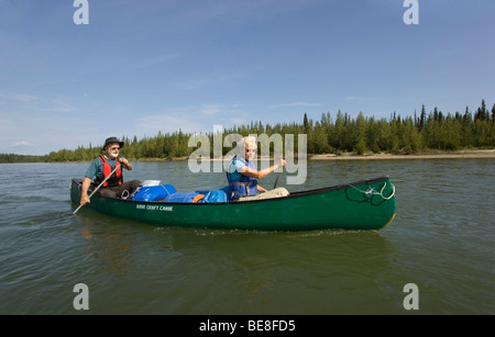Older couple, man and woman paddling a canoe, canoeing, upper Liard River, Yukon Territory, Canada - Stock Photo