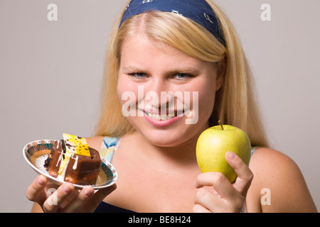Young fat woman hesitate what to eat. - Stock Photo