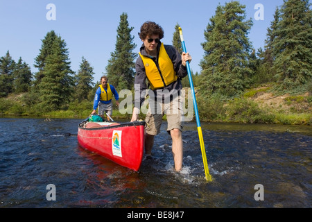Two man lining canoe, walking bare feet in clear, shallow water of Caribou Creek, upper Liard River, Yukon Territory, - Stock Photo