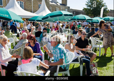 People relaxing and eating under umbrellas in the sun at Ludlow Food Festival Shropshire England UK - Stock Photo