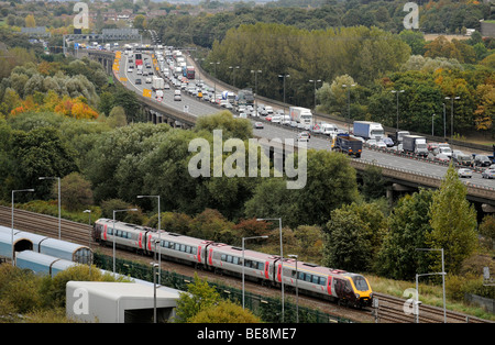 A  COMMUTER TRAIN RUNNING NEXT TO QUEUING TRAFFIC ON THE ELEVATED M6 MOTORWAY NORTHBOUND NEAR BIRMINGHAM ,UK - Stock Photo