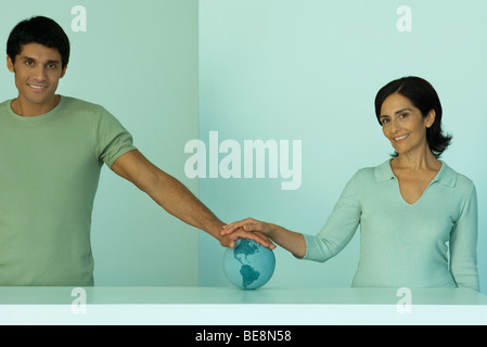 Man and woman with hands placed together on globe - Stock Photo