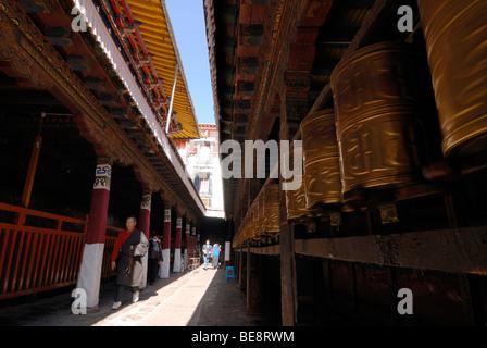 Tibetan prayer wheels, prayer cylinders, and Buddhist pilgrims, elderly man, in the course of the circumnavigation - Stock Photo