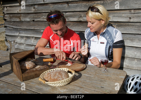 Bicycle racers taking a break with South Tyrolean bacon and wine at the mountain lodge on the Passo di Pennes, South - Stock Photo