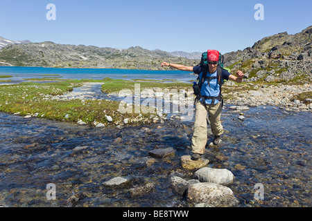Young woman crossing a creek, hiking, backpacking, hiker with backpack, historic Chilkoot Trail, Chilkoot Pass, - Stock Photo